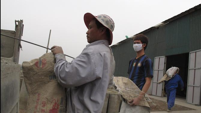 In this Jan. 18, 2013 photo, workers haul cement into a warehouse on disputed land in Kim Son village, Vietnam. Forced evictions are one of the main drivers of public anger against Vietnam's Communist leadership.  Land disputes break out elsewhere in Asia, notably next door in China, but they have particular resonance in Vietnam, where wars and revolutions were fought in the name of the peasant class to secure collective ownership of the land. (AP Photo/Chris Brummitt)
