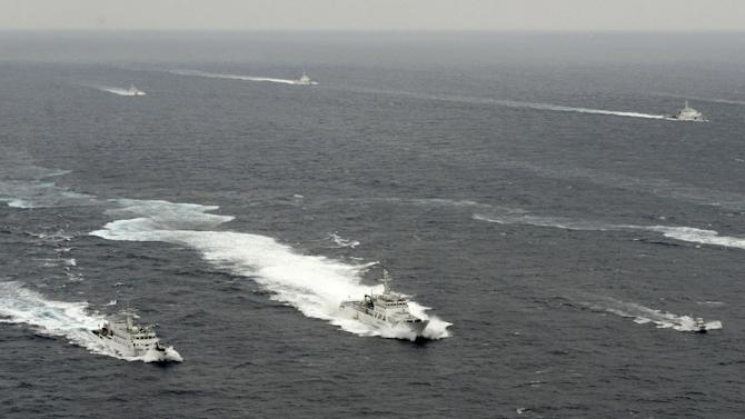 A  Japan Coast Guard vessel, bottom center, sails between a Chinese surveillance ship, bottom left, and a Japanese fishing boat, bottom right, near disputed islands called Senkaku in Japan and Diaoyu in China in the East China Sea Tuesday, April 23, 2013. A group of Japanese ultra-nationalists planned Tuesday to approach the islands on several fishing vessels and pleasure boats. The visit adds to risks of confrontation, however, with Chinese vessels circulating in the area. (AP Photo/Kyodo News) JAPAN OUT, MANDATORY CREDIT, NO LICENSING IN CHINA, HONG KONG, JAPAN, SOUTH KOREA AND FRANCE