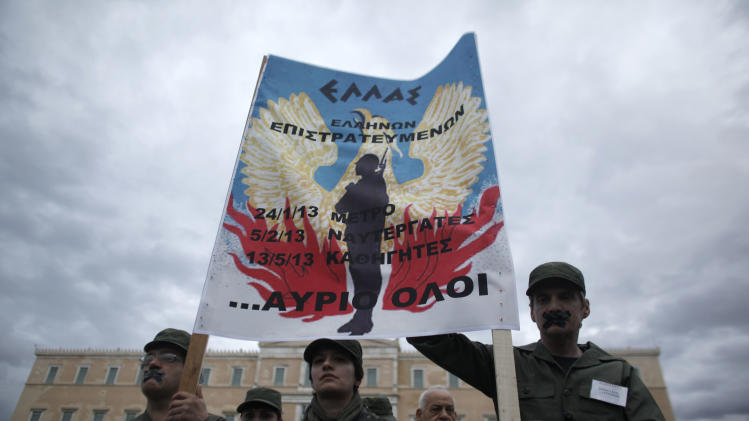 """Greek state school teachers dressed in army fatigues to mock a civil mobilization order hold a banner comparing government policies to those of the Greece's 1967-74 military dictatorship, during a peaceful protest in central Athens on Monday, May 13, 2013. The banner, over the insignia of the dictatorship, reads: """"A Greece of Mobilized Greeks, Metro Employees, Ferry Crews, Teachers - Tomorrow Everyone."""" Greece's conservative-led government has issued a civil mobilization order forcing state school teachers to work during university entrance exams later in May. Teachers' unions had been planning strikes during the exams, to protest planned increases in working hours and involuntary staff transfers _ as part of the financially-distressed country's austerity and reform program.  (AP Photo/Kostas Tsironis)"""
