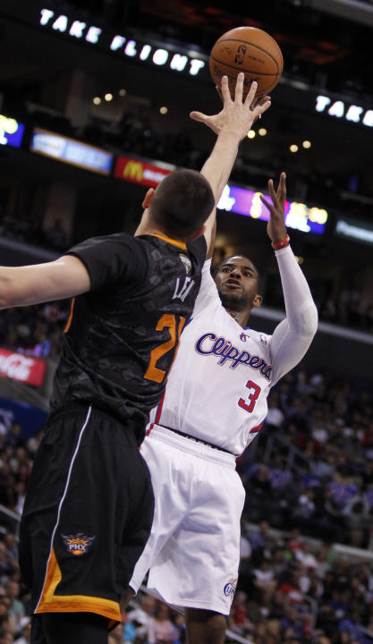 Los Angeles Clippers guard Chris Paul (3) shoots over Phoenix Suns center Alex Len, left, of Ukraine during the first half of an NBA basketball game Monday, March 10, 2014, in Los Angeles. (AP Photo/A