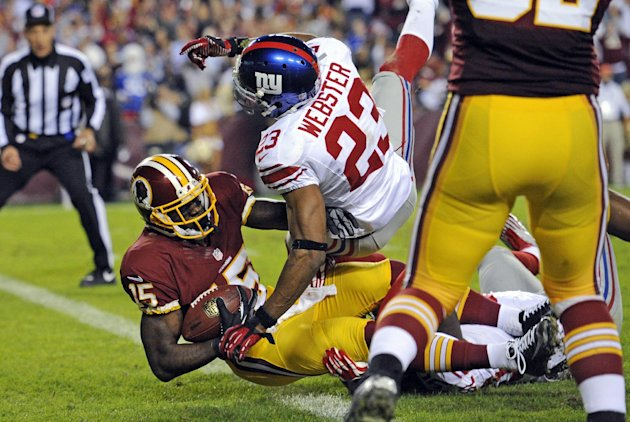 Washington Redskins wide receiver Josh Morgan (15) falls into the end zone for a touchdown under pressure from New York Giants cornerback Corey Webster (23) during the first half of an NFL football ga