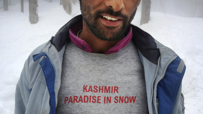 In this photo taken Saturday, Feb. 23, 2013, a Kashmiri worker wears a T-shirt at Gulmarg, Kashmir. Gulmarg, a ski resort nestled in the Himalayan mountains in Indian-held Kashmir is one of the most militarized places on earth. (AP Photo/Kevin Frayer)