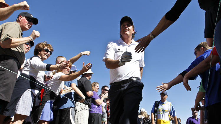 Phil Mickelson walks through a gauntlet of fans trying to give him a high-five as he walks to the third tee during the second round of the Waste Management Phoenix Open golf tournament Friday, Feb. 1, 2013, in Scottsdale, Ariz. (AP Photo/Ross D. Franklin)