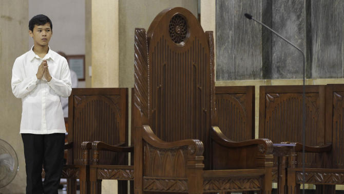 A Filipino Catholic altar boy stands beside an empty priest' chair during a mass at the Shrine of Our Lady of Perpetual Help in suburban Paranaque, south of Manila, Philippines on Sunday March 3, 2013. Filipinos in Asia's largest predominantly Roman Catholic nation on Sunday went to church that awkwardly had no pope for the first time in 600 years and prayed for the smooth rise of a successor to Benedict XVI who can lead an embattled church. (AP Photo/Aaron Favila)
