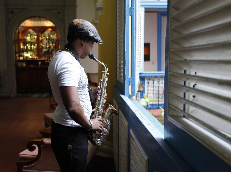 In this picture taken on April 17, 2012, a musician rehearses beside a louvered window at a restaurant in Old Havana, Cuba. (AP Photo/Kathy Willens)
