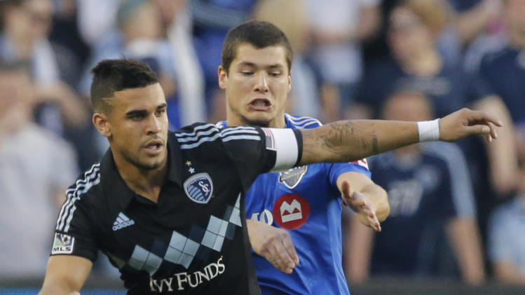 Sporting KC forward Dom Dwyer (14) works the ball forward while covered by Montreal Impact defender Karl Ouimette (34) during the first half of an MLS soccer match in Kansas City, Kan., Saturday, April 19, 2014. (AP Photo/Orlin Wagner)
