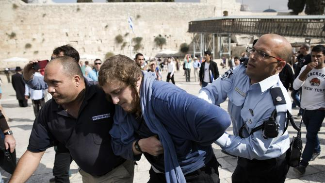 An Israeli right wing activist is detained by police at the Western Wall inside the old city of Jerusalem