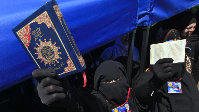 An Egyptian supporter of Hazem Abu Ismail, who was barred from the presidential race because his mother held American citizenship, holds a copy of the Quran, the Muslim holy book, during a demonstration at Tahrir Square, the focal point of Egyptian uprising, in Cairo, Egypt, Friday April 20, 2012. Tens of thousands of protesters packed Cairo's downtown Tahrir Square on Friday in the biggest demonstration in months against the ruling military, aimed at stepping up pressure on the generals to hand over power to civilians and bar ex-regime members from running in upcoming presidential elections. (AP Photo/Amr Nabil)