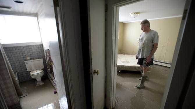 Homeowner Glenn Tibbles looks at the damage done by floodwaters to his home near downtown Calgary, Alberta, on Sunday, June 23, 2013. About 65,000 residents of Calgary were being allowed to return to their homes Sunday to assess the damage from flooding that has left Alberta's largest city awash in debris and dirty water. (AP Photo/The Canadian Press, Jonathan Hayward)