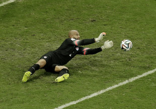 Tim Howard makes one of his 16 saves against Belgium on Tuesday. (AP)