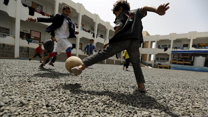 Boys play soccer at the yard of a school sheltering people displaced by Saudi-led air strikes on Yemen's northwestern province of Saada, in the capital Sanaa