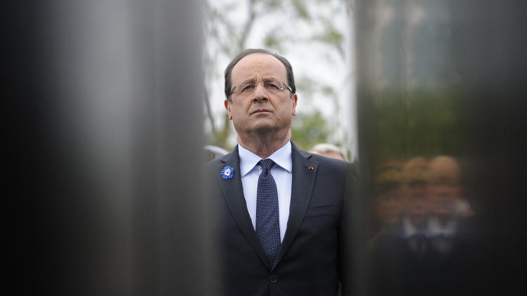 French President Francois Hollande listens to national anthems by the Charles De Gaulle monument during a ceremony marking the 68th anniversary of the end of World War II in Europe, in Paris, Wednesday, May 8, 2013. (AP Photo/Yoan Valat, Pool)