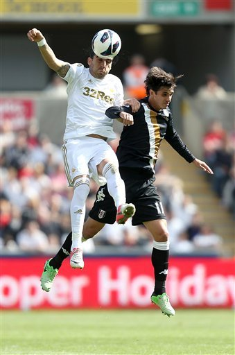 Swansea City's Chico Flores, left, and Fulham's Bryan Ruiz battle for the ball during the English Premier League soccer match at the Liberty Stadium, Swansea, Wales, Sunday May 19, 2013