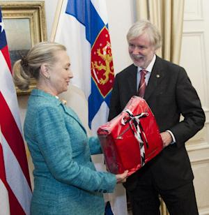 FILE - In this June 27, 2012 file-pool photo, then-Secretary of State Hillary Rodham Clinton receives a gift from Finnish Foreign Minister Erkki Tuomioja at the Government Banquet Hall in Helsinki, Finland. Former Secretary of State Hillary Rodham Clinton has outpaced President Barack Obama when it comes to lavish gifts from foreign leaders. State Department documents released Friday show Clinton got gold jewelry worth a half-million dollars from King Abdullah of Saudi Arabia, while Obama's most expensive gift was a $16,500 gold-plated clock from Crown Prince Salman bin Abdulaziz al-Saud, the Saudi defense minister. The gifts were among a bounty of vases, watches, art work and other items given to top U.S. officials in 2012, according to the department's Office of Protocol, which catalogs the gifts and publishes an annual listing. (AP Photo/Haraz N. Ghanbari, Pool)