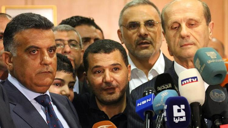 Lebanese security official Major General Abbas Ibrahim (L) and Interior Minister Marwan Charbel (R) pictured at Beirut airport on September 26, 2012 with a pilgrim taken hostage by rebels in the northern Syria in May