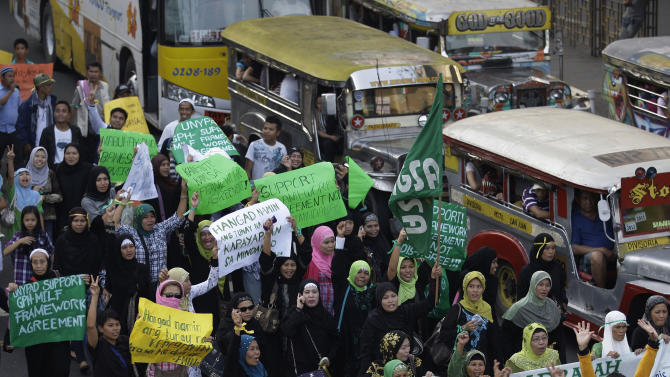 Filipino Muslim women march during a rally outside the Malacanang presidential palace in Manila, Philippines on Sunday Oct. 14, 2012. Philippine officials and rebels say about 200 Muslim guerrillas led by their elusive chief have arrived in Manila for the signing of a preliminary peace pact to end one of Asia's longest-running insurgencies. (AP Photo/Aaron Favila)