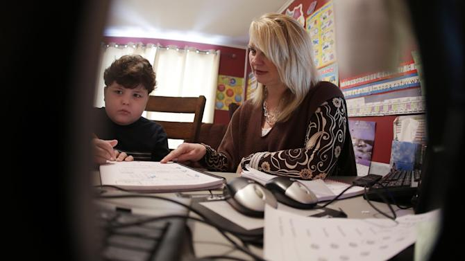 In this Tuesday, Jan. 22, 2013 photo, Devon Carrow works with teacher Sheri Voss while attending school from home while operating a robot in the classroom, in Orchard Park N.Y. Carrow's life-threatening allergies don't allow him to go to school. But the 4-foot-tall robot with a wireless video hookup gives him the school experience remotely, allowing him to participate in class, stroll through the hallways, hang out at recess and even take to the auditorium stage when there's a show.  (AP Photo/David Duprey)