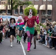Competitors run in the stiletto-sprint at the Drag Queen Olympics in Amsterdam on August 3. Men in black leather shorts and little else, others in pink and silver body paint and drag queens in flamboyant dresses took to Amsterdam's canals Saturday for the annual Gay Pride parade