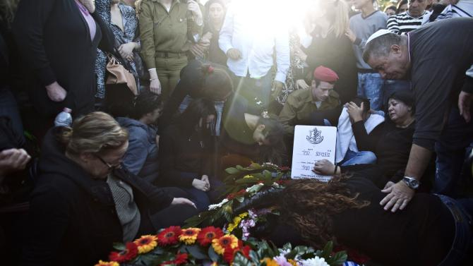 The mother, relatives and friends of Israeli soldier Dor Nini mourn over his fresh grave during his funeral in a cemetery at Shtulim village near Ashdod
