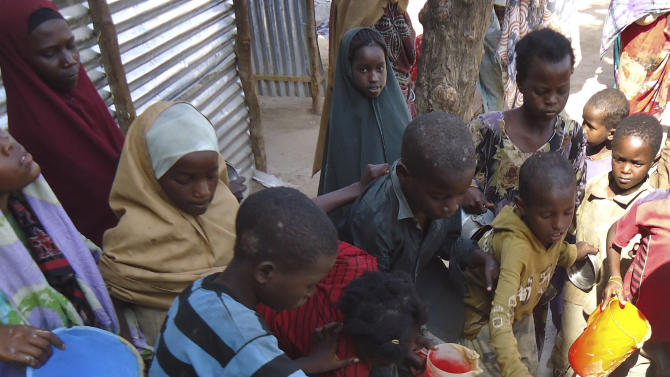 Children from southern Somalia get cooked food at a local NGO's compund in Mogadishu, Somalia, Wednesday, Sept.14, 2011. A massive aid operation is currently underway to help millions of Somalis affected by the fighting and a famine caused by severe drought. (AP Photo/Ali Bashi)