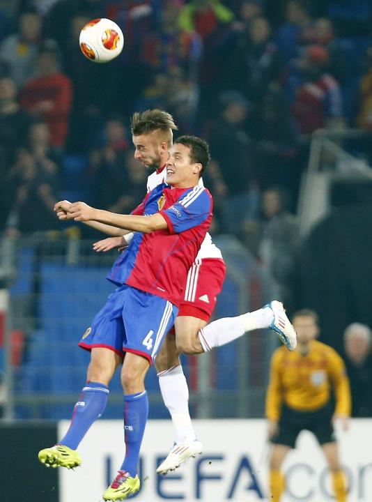 FC Basel's David Degen jumps for the ball with Svento of FC Salzburg during their Europa League round of 16 soccer match at St.Jakob-Park stadium in Basel