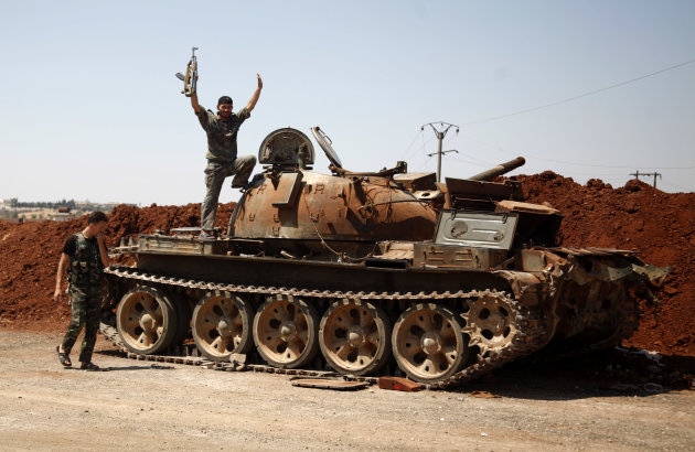 A Free Syria Army fighter waves from the top of a destroyed army tank in the town of Anadan on the outskirts of Aleppo, Syria, Monday, Aug. 6, 2012. (AP Photo)