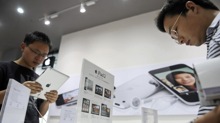 In this photo taken on Friday, May 6, 2011, customers try out iPad tablet computer at a Apple's authorized dealer outlet in Changsha in south China's Hunan province. Authorities have seized iPads from more Chinese retailers in February 2012 in an escalating trademark dispute between Apple Inc. and a struggling local company that could disrupt global sales of the popular tablet computer. (AP Photo) CHINA OUT