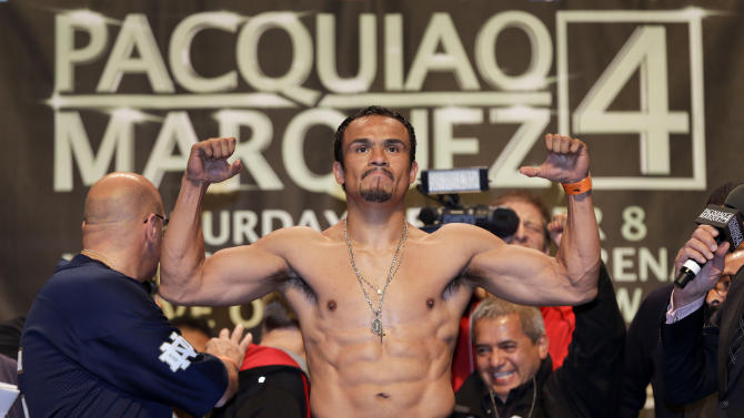 Juan Manuel Marquez flexes his muscles for the crowd during the weigh-in for his welterweight fight against Manny Pacquiao, Friday, Dec. 7, 2012, in Las Vegas. Marquez will face Pacquiao on Saturday in Las Vegas. (AP Photo/Julie Jacobson)
