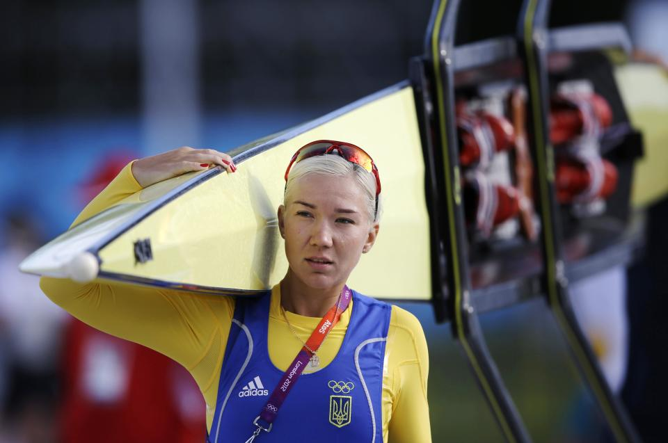 Anna Kravchenko of Ukraine's women's double scull team, carries her boat in Eton Dorney, near Windsor, England, at the 2012 Summer Olympics, Sunday, July 29, 2012. (AP Photo/Chris Carlson)