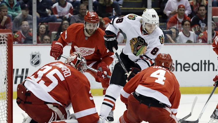 Chicago Blackhawks right wing Patrick Kane (88) tries to get around Detroit Red Wings defenseman Jakub Kindl (4), of the Czech Republic, to shoot on goalie Jimmy Howard (35) during the first period in Game 6 of the Western Conference semifinals in the NHL hockey Stanley Cup playoffs in Detroit, Monday, May 27, 2013. (AP Photo/Paul Sancya)