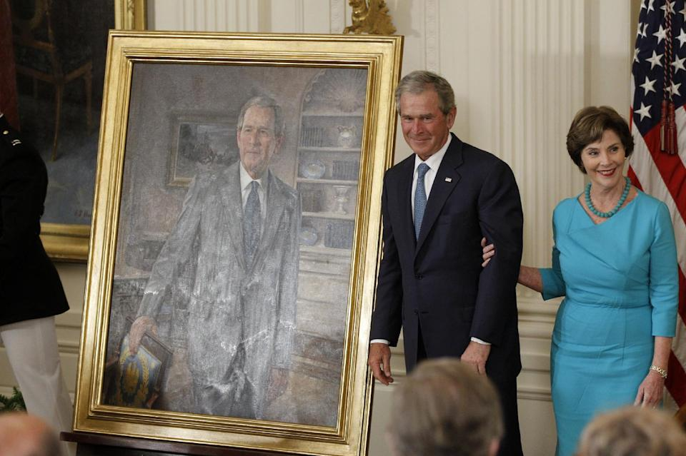Former President George W. Bush and his wife Laura stand next to his portrait during a unveiling ceremony, Thursday, May 31, 2012, in the East Room of the White House in Washington.  (AP Photo/Charles Dharapak)
