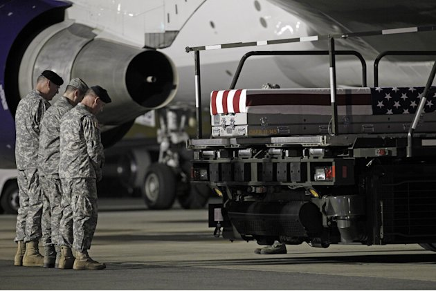 Chaplain Col. Dennis Goodwin, left, directs a prayer over the transfer case containing the remains of Army Capt. Bruce K. Clark of Spencerport, N.Y., upon arrival at Dover Air Force Base, Del. on Thur
