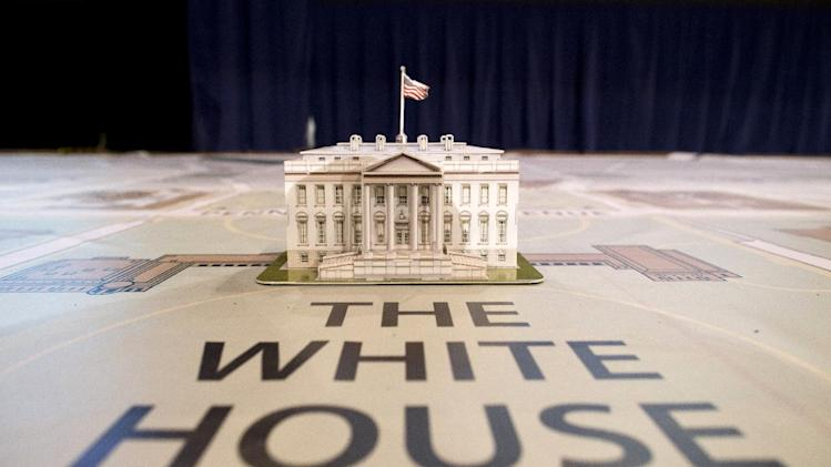 In this Dec. 12, 2012, photo, a model of the White House sits on a giant map during a media tour highlighting inaugural preparations being made by the Joint Task Force-National Capital Region for military and civilian planners  at the DC Armory in Washington. The Presidential Inaugural Committee has begun sending out invitations to groups nationwide to march behind Obama from his swearing in at the Capitol to the White House on Jan. 21. The first wave selected includes the marching band from Miami University of Ohio, the alma matter of GOP vice presidential nominee Paul Ryan where first lady Michelle Obama spoke during the final weekend of the campaign. Also selected was the Virginia Military Institute that is a traditional performer in inaugural parades. (AP Photo/ Evan Vucci)