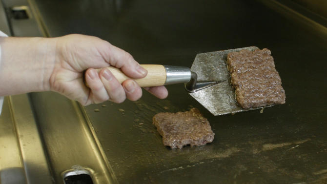 In this Sept. 15, 2011 photo, Liz Shires, Wendy's research and development laboratory coordinator, works on cooking two hamburger patties for the new Dave's Hot 'N Juicy Cheeseburger in the lab at the company's international headquarters in Dublin, Ohio. (AP Photo/Paul Vernon)