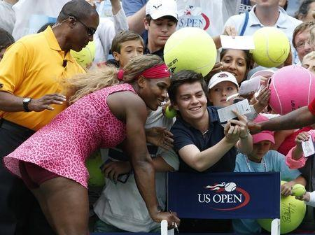 Serena Williams of the U.S. poses for a picture with a fan after her win over compatriot Varvara Lepchenko during their match at the 2014 U.S. Open tennis tournament in New York