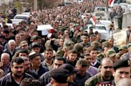 A handout picture released by the official Syrian Arab News Agency (SANA) shows the funeral procession of Syrian Colonel Ali Deeb, reportedly killed in recent violence in the country, in the coastal town of Tartus