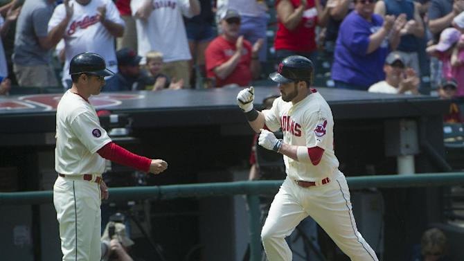 Cleveland Indians' Jason Kipnis, right, heads to home plate and is greeted by third base coach Mike Harbaugh after hitting a home run off Toronto Blue Jays' Drew Hutchinson during the third inning of a baseball game in Cleveland, Sunday, May 3, 2015. (AP Photo/Phil Long)