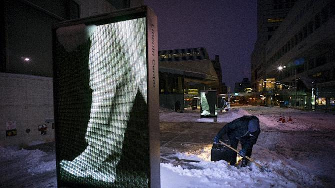 Snow is cleared from a sidewalk at Lincoln Center early Tuesday, Jan. 27, 2015, in New York, after a snowfall shut down parts of the Northeast with blizzard in parts of the region. A storm packing blizzard conditions spun up the East Coast early Tuesday, pounding coastal eastern Long Island into Maine with high winds and heavy snow.  (AP Photo/Craig Ruttle)