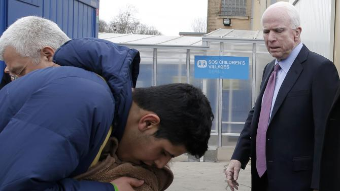 U.S. Senator McCain looks at a migrant and his child during his visit at a train station in the town of Sid