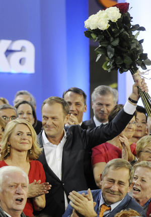 Prime Minister Donald Tusk celebrates with his wife Malgorzata, left, as the first exit poll is published during the election party of Tusk's Civic Platform, a centrist and pro-EU party,  in Warsaw Sundey, Oct. 9, 2011. An exit poll shows that the centrist Civic Platform party of Prime Minister Donald Tusk is winning Poland's national election with 39.6 percent of the votes. (AP Photo/Alik Keplicz)