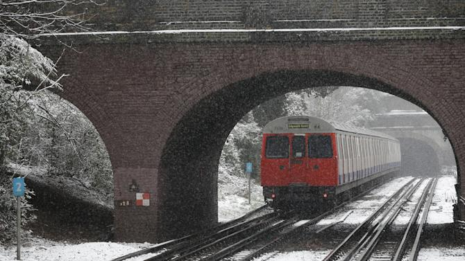 A London Underground train arrives at a station in south London, during snowfall, Sunday, Jan. 20, 2013. (AP Photo/Lefteris Pitarakis)