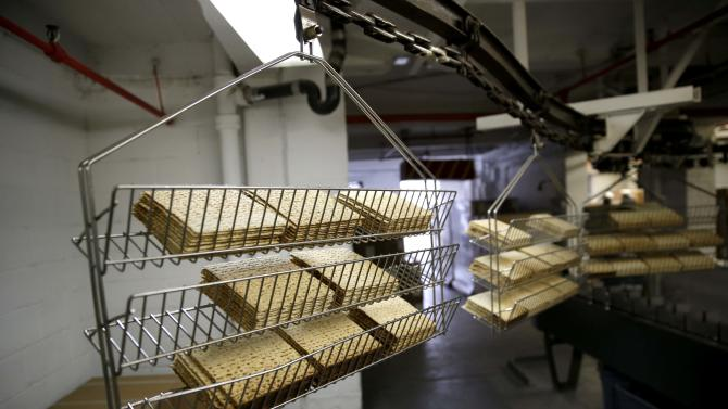 Matzos straight from the oven are ferried on racks to where they will be packaged at the Streit's matzo factory in New York, Wednesday, March 4, 2015. (AP Photo/Seth Wenig)