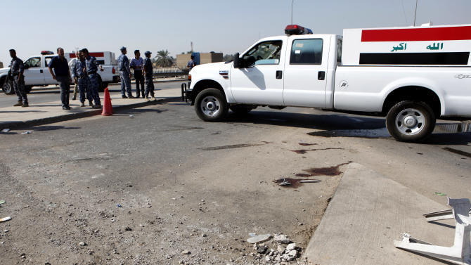 Iraqi security forces inspect the scene of a roadside bomb, which exploded in northern Baghdad, Iraq, Wednesday, Oct. 27, 2010. Iraqi police say a bombing at a checkpoint near the headquarters of a Sunni foundation in north Baghdad has killed security guards. (AP Photo/Hadi Mizban)
