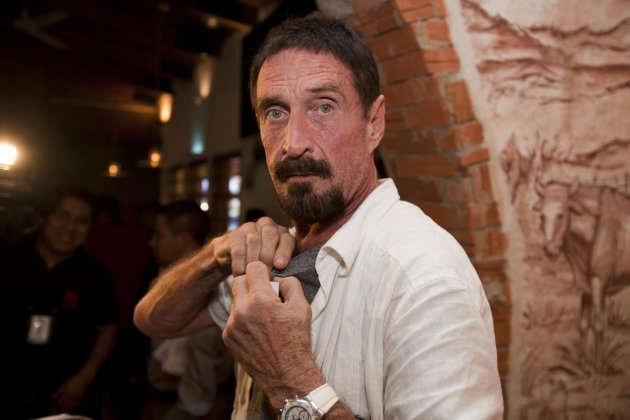 "Software company founder John McAfee adjusts a microphone in preparation for an interview in Guatemala City, Tuesday, Dec. 4, 2012.  McAfee, 67, has been identified as a ""person of interest"" in the ki"