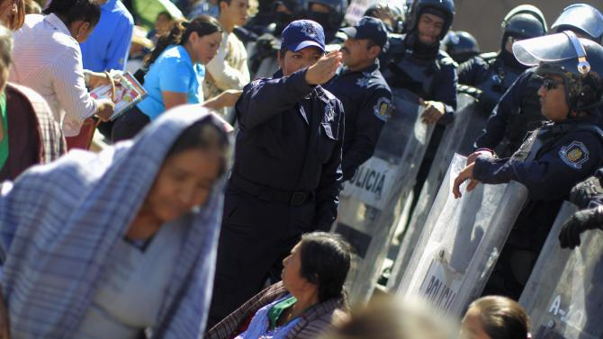 A police officer instructs people to clear the area during a protest by indigenous people outside the government palace of Guerrero state in Chilpancingo