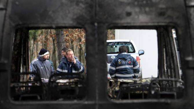 Employees  of Hellas Gold, are seen through a burnt van  at a mining facility  near the village of Skouries, located on the northern peninsula of Halkidiki Greece, on Sunday, Feb. 17 2013.  About 40 masked attackers raided the facilities of a prospective gold mine in northern Greece overnight Sunday, setting machinery and offices alight, authorities said. There has long been opposition to the prospect of a gold mine and processing plant being built at Skouries in the Halkidiki peninsula, with some residents objecting to what they say will be the destruction of the environment and of pristine forest in the area, leading to the loss of tourism and other local activities such as farming, the rearing of livestock and fishing. (AP Photo/Nikolas Giakoumidis)
