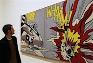 A worker poses with pop artist Roy Lichtenstein&#39;s Whaam!, 1963, during a media viewing of the Lichtenstein: A Retrospective exhibition, at Tate Modern in London February 18, 2013. The exhibition which opens on February 21 runs until May 27. REUTERS/Luke MacGregor