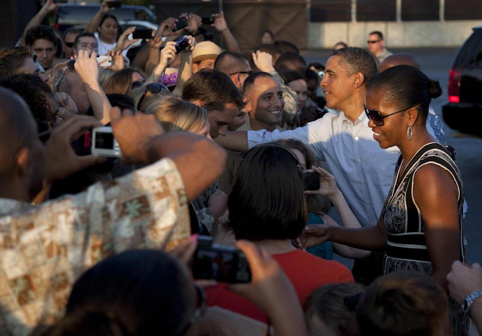 President Barack Obama and first lady Michelle Obama greet people on the tarmac before they board Air Force One at Hickam Air Force Base in Monday, Jan. 2, 2012, in Honolulu, en route to Washington after a family vacation. (AP Photo/Carolyn Kaster)