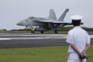 A member of the Japanese Self Defense Force watches as a U.S. Navy F/A-18E Super Hornet takes off during carrier landing training on Iwo Jima, Japan, Friday, June 7, 2013. Though the U.S. Navy regularly conducts carrier landing training on Iwo Jima, now known in Japan as Ioto, officials say the island is not up to Navy safety standards, and that a new site is needed. (AP Photo/Greg Baker)