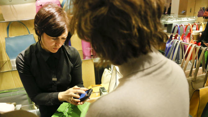 In this Friday, Feb. 15, 2013, photo, a sales staff member at Barney's New York uses an iPod Touch to help a customer make a purchase, in New York. Stores across the country are ditching the old-fashioned, clunky cash registers and instead having salespeople _ and shoppers themselves _ checkout on smartphones and tablet computers. (AP Photo/Bebeto Matthews)